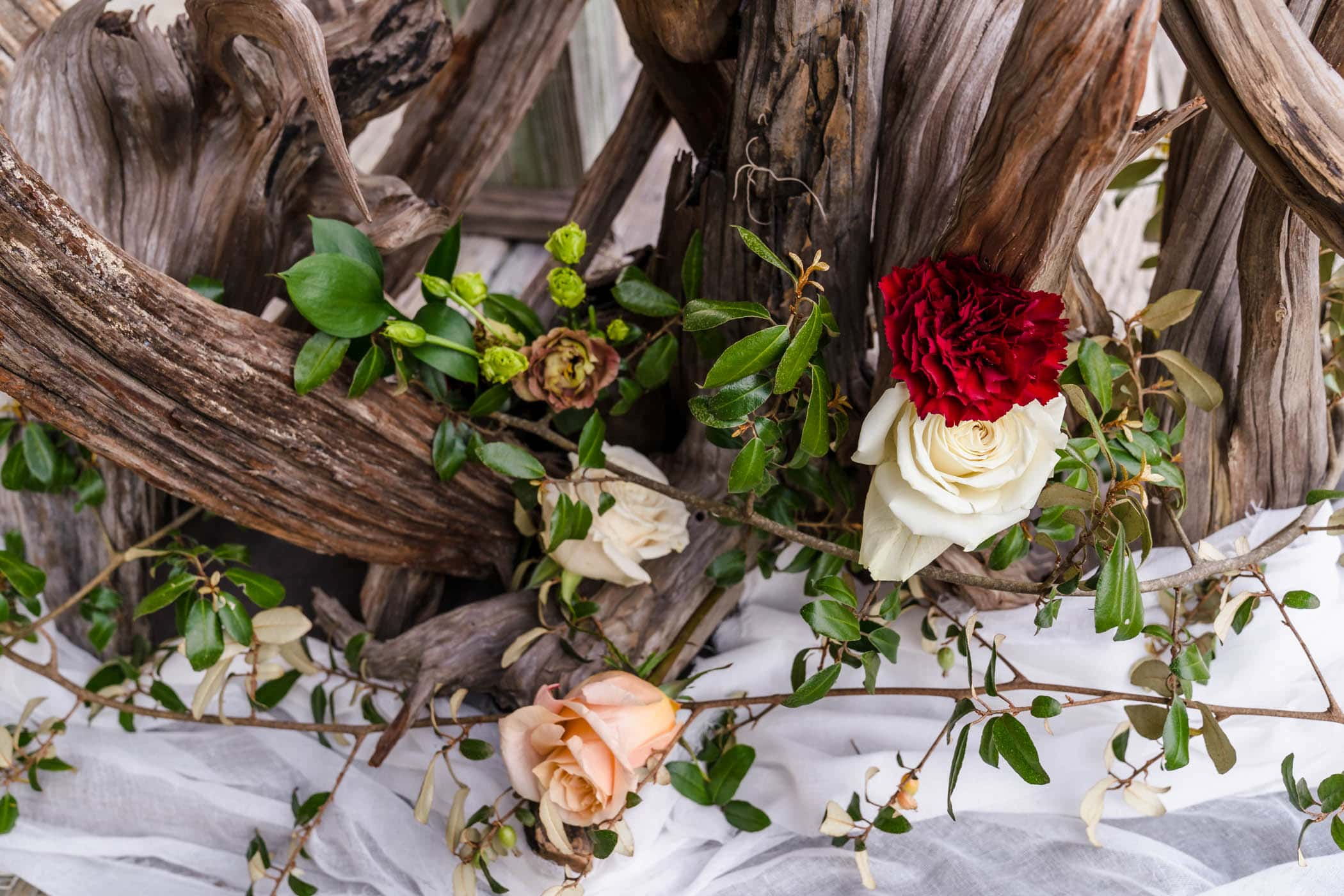 florals on driftwood arch for wedding ceremony