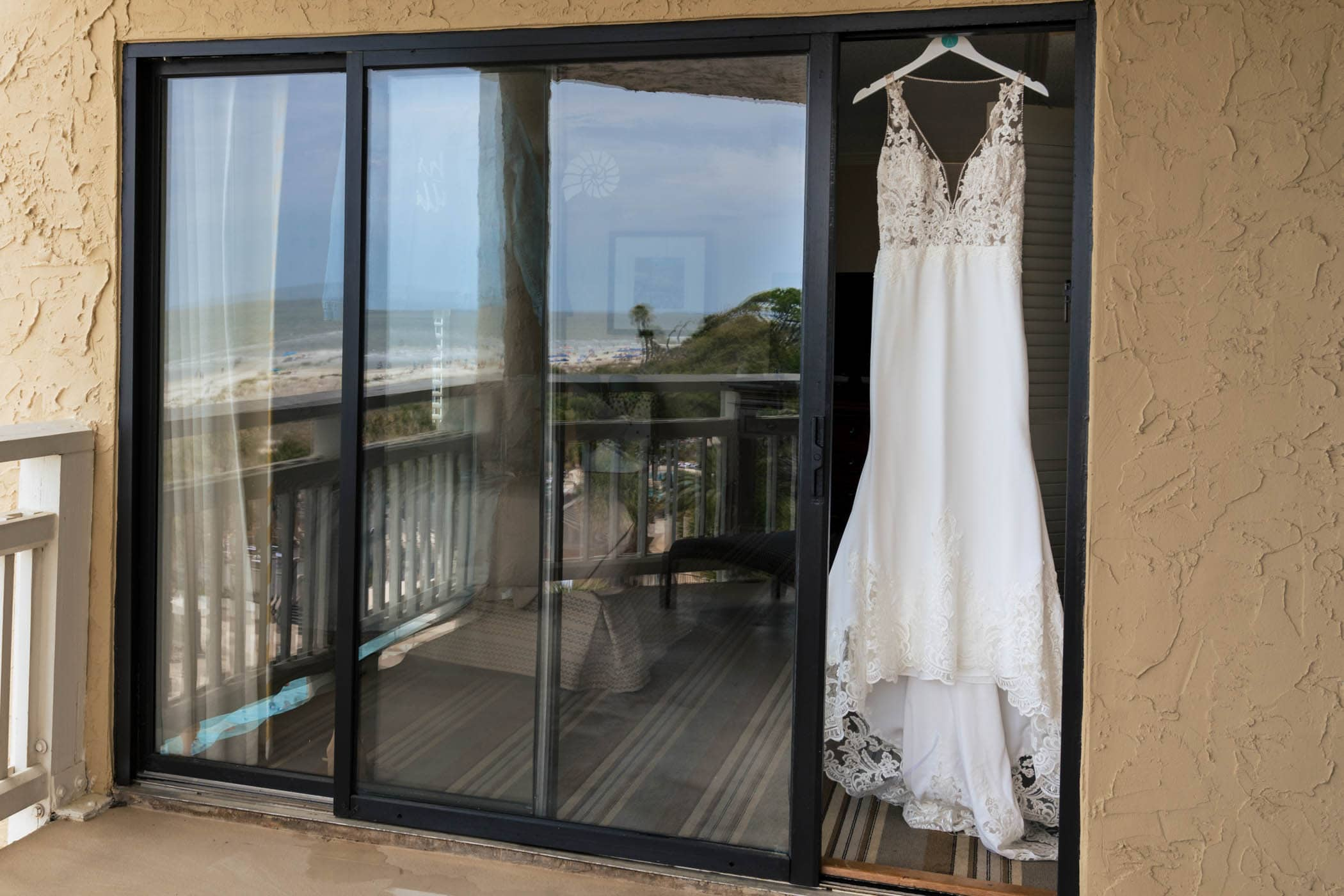 Wedding Dress with Beach refection in sliding glass doors