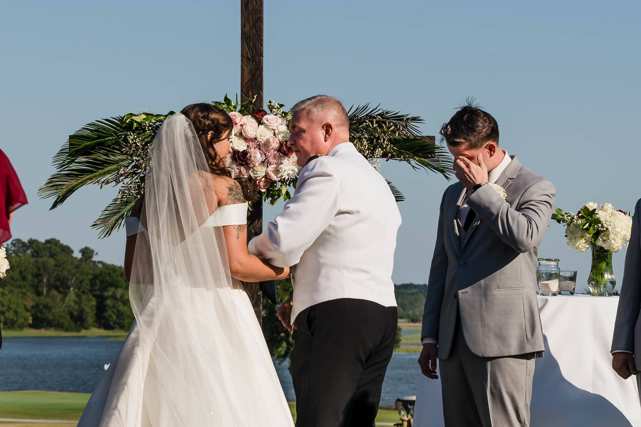 Groom wiping tears from his eyes as bride walks up with her father by Susan DeLoach Photography SC wedding photographers