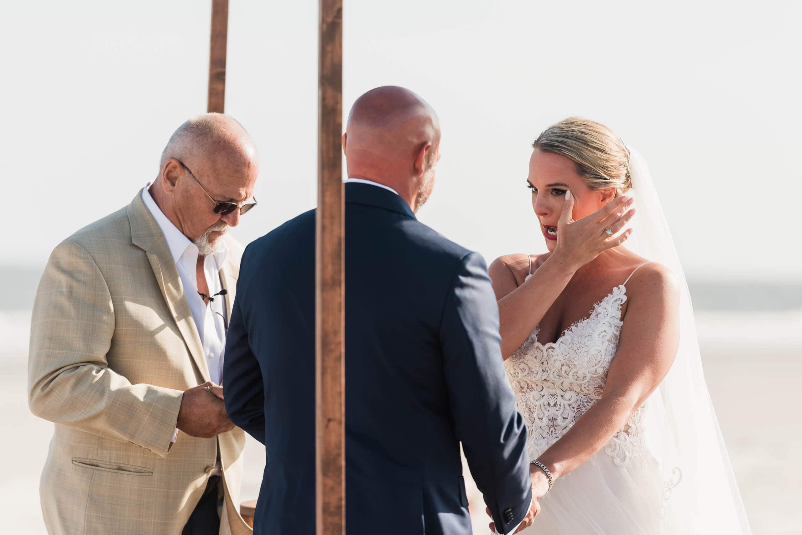 Bride wiping tear from her cheek during beach wedding ceremony on Fripp Island by Susan DeLoach Photography SC Wedding Photographer