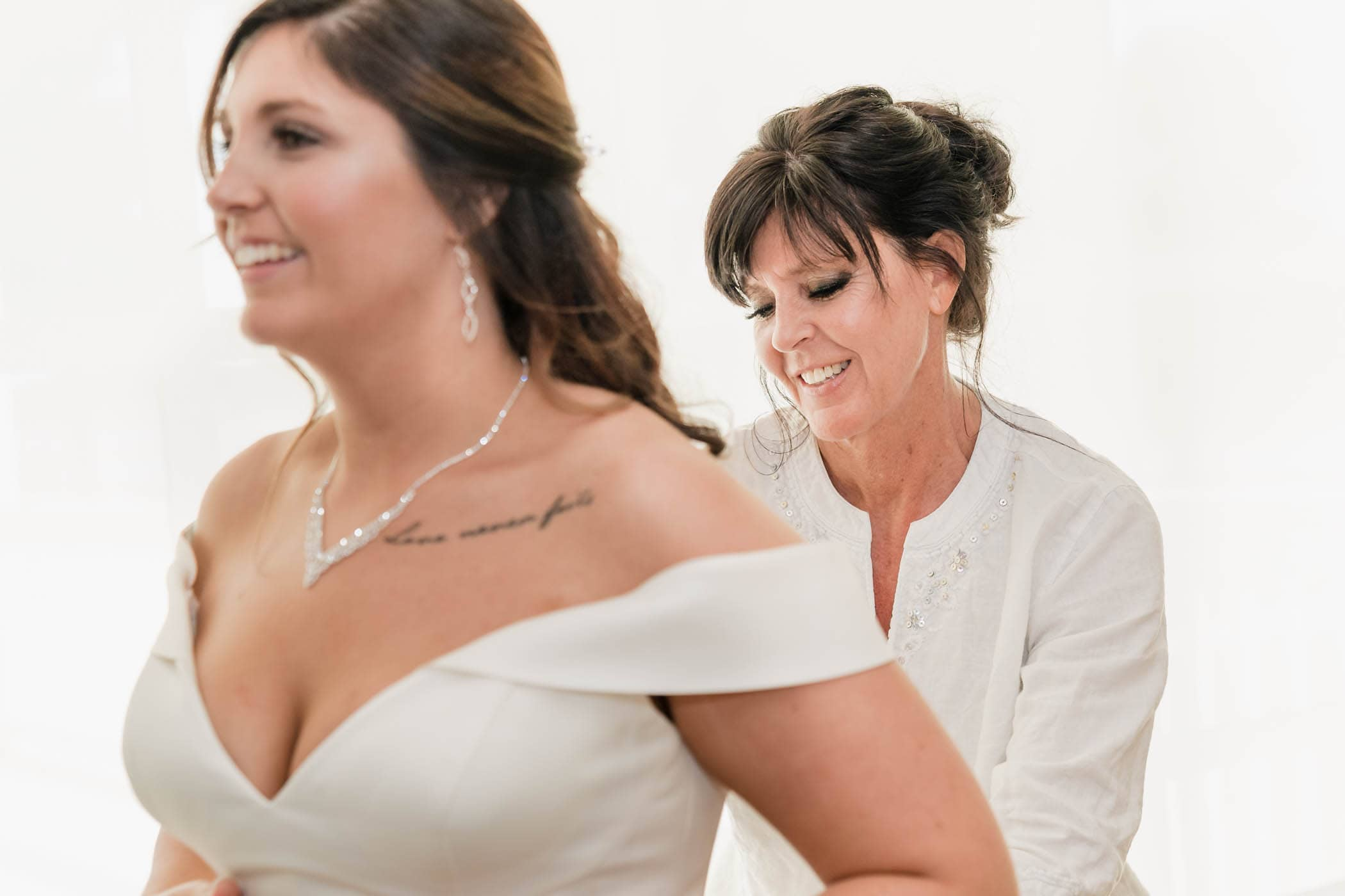 Mother of the bride helping her daughter with her dress by Susan DeLoach Photography SC wedding photographers