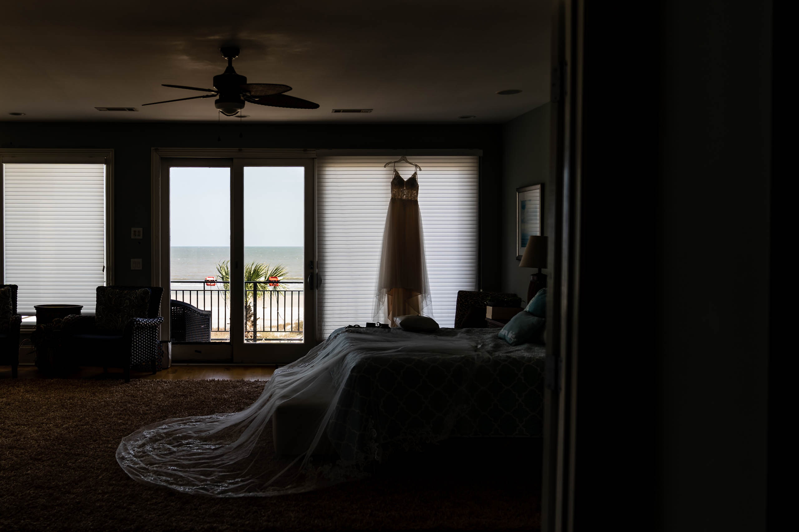Wedding dress hanging in window of beach house on Fripp Island by susan deloach photography sc wedding photographer
