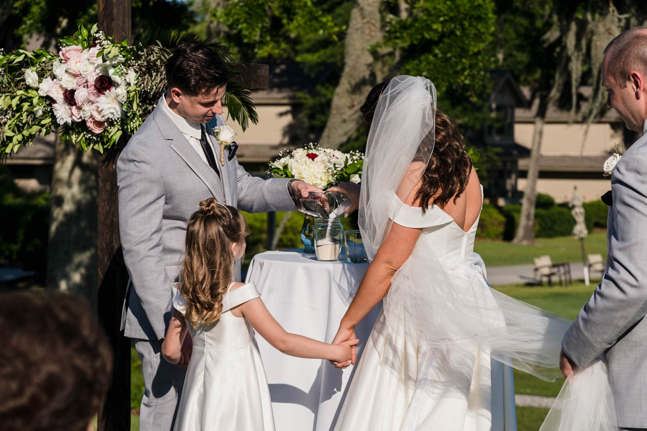 Bride, groom and daughter during sand ceremony at wedding Dataw Island Club House by Susan DeLoach Photography SC wedding photographers