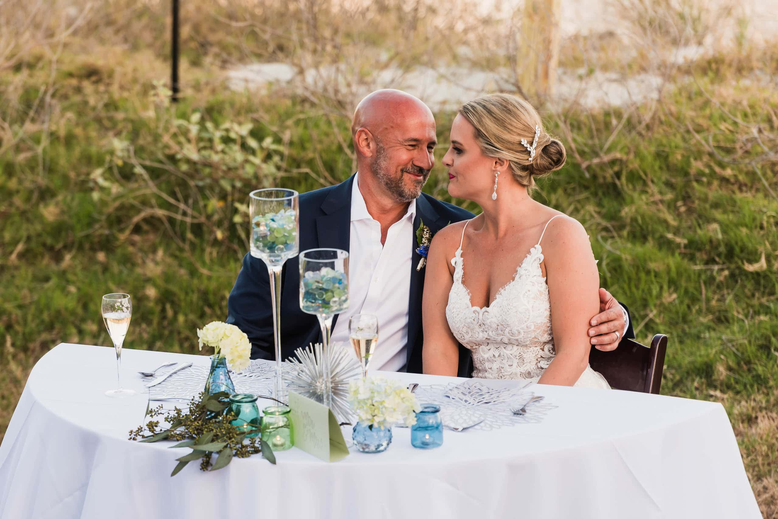 Bride and Groom sitting at the sweetheart table during wedding reception on the beach at Fripp Island by Susan DeLoach Photography SC Wedding photographer