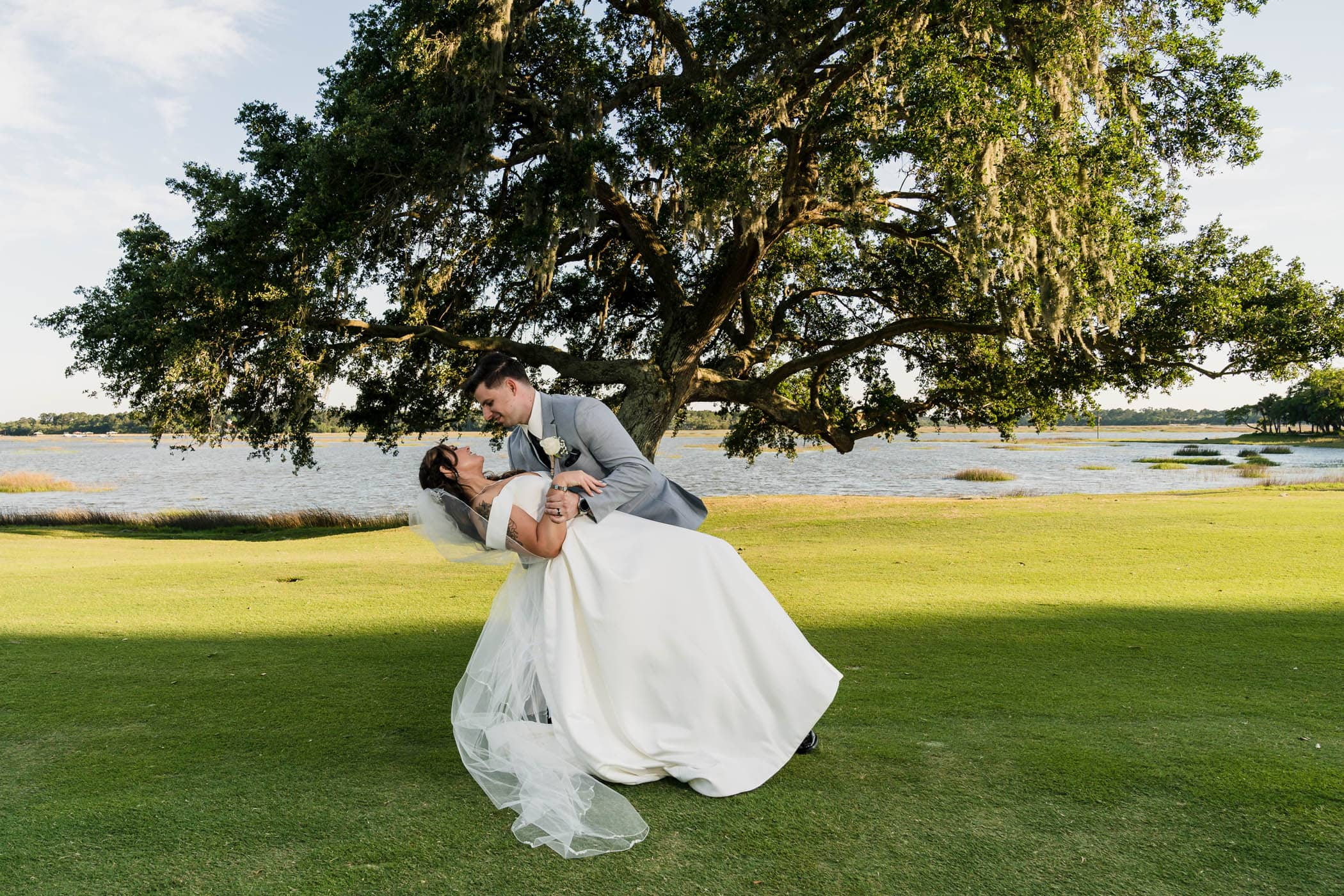 Groom dipping bride on the golf course at Dataw Island Club House by Susan DeLoach Photography SC wedding photographers