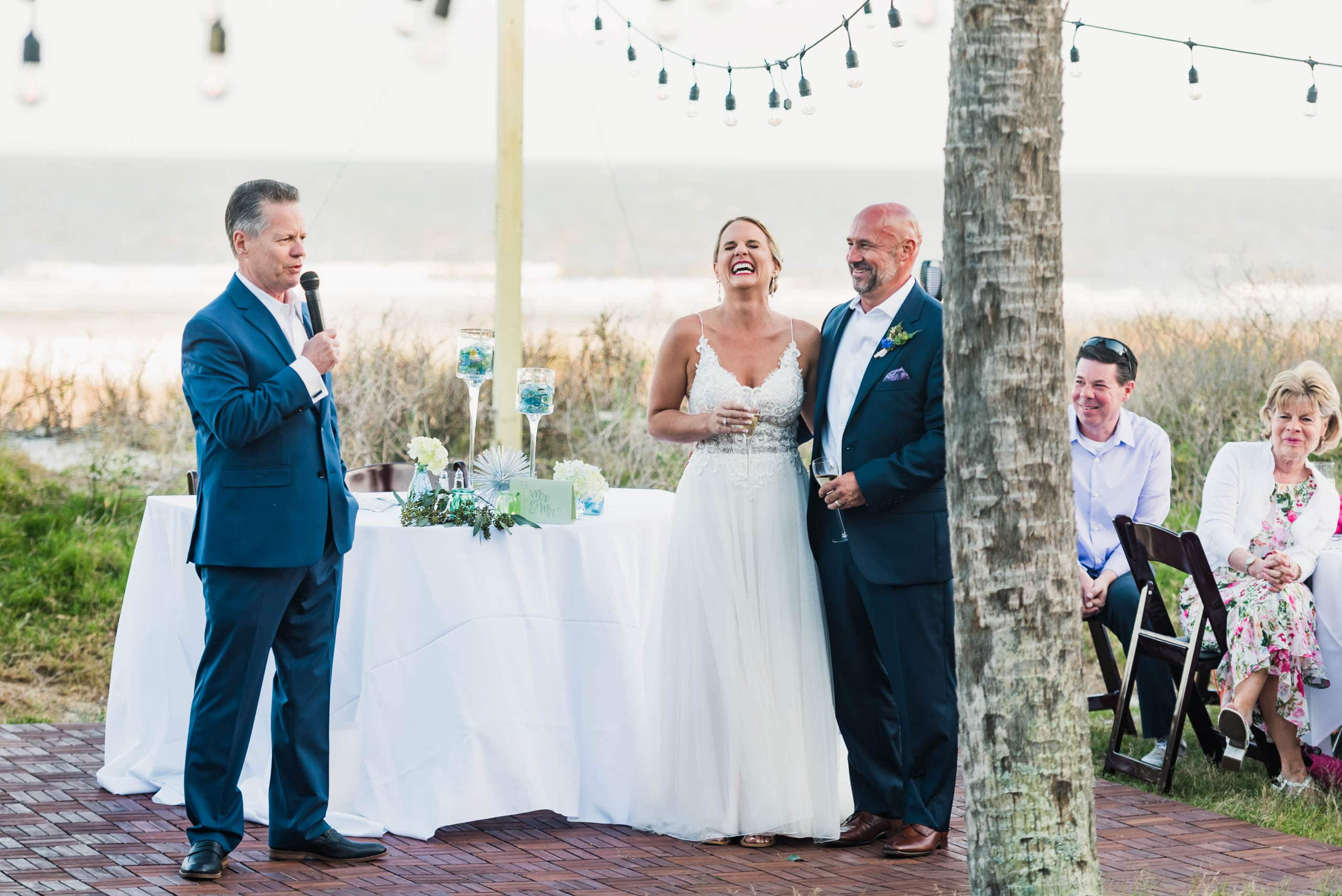 Bride and Groom laughing during speech given by the father of the bride at a beach wedding on Fripp Island By Susan DeLoach Photography SC Wedding Photographer