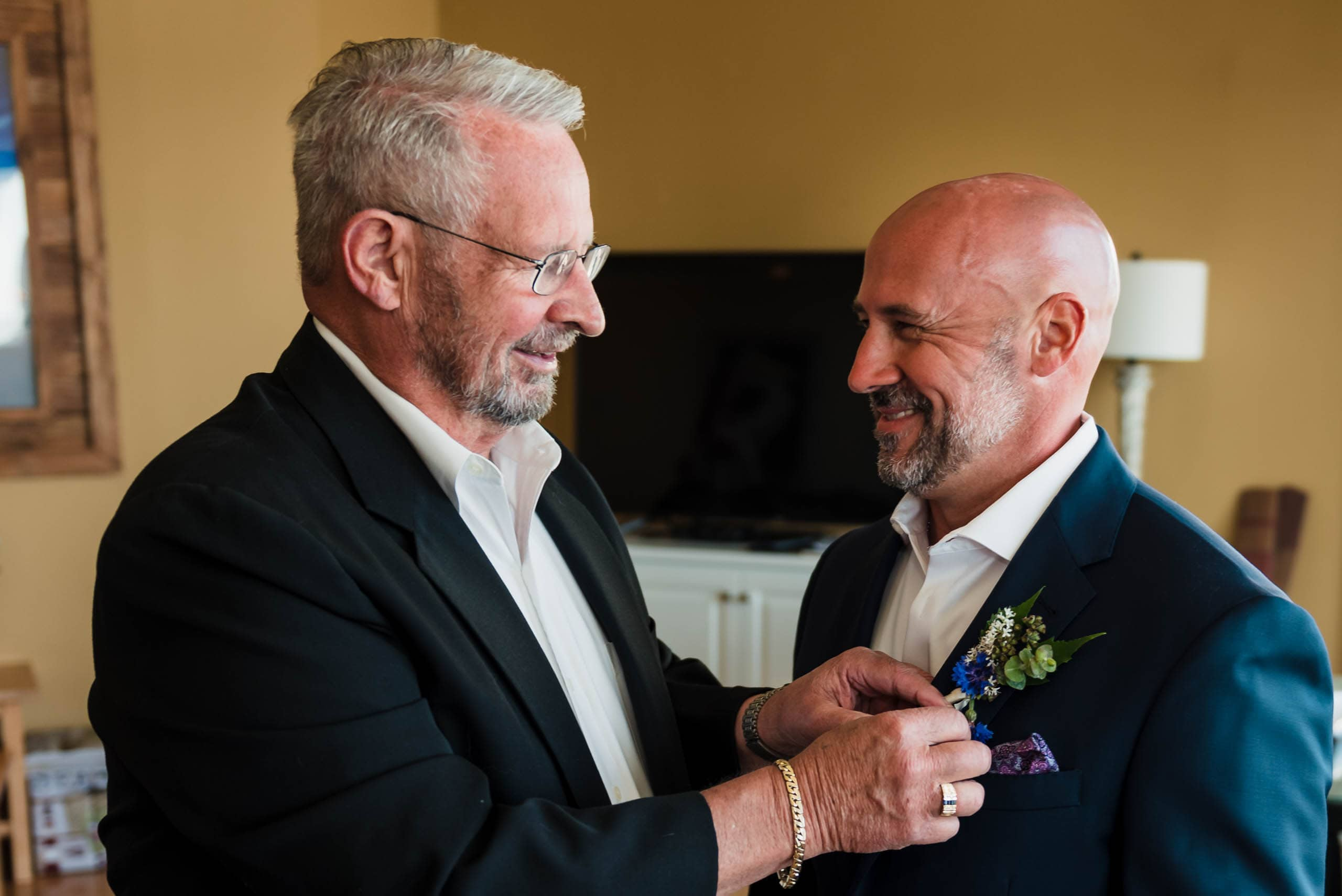 father of the groom pinning boutonniere on groom at Fripp Island Beach Wedding by Susan DeLoach Photography SC wedding photographer