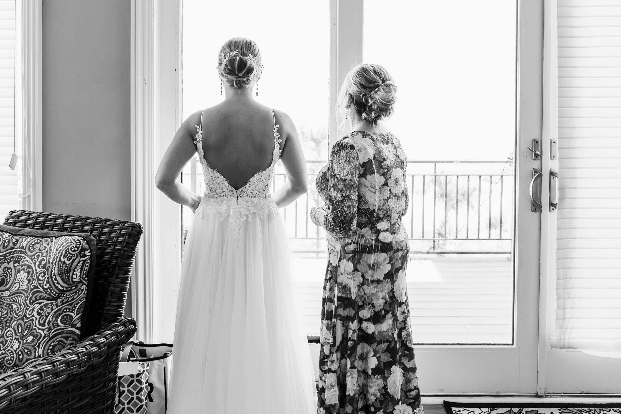 Bride in wedding dress looking out of a window at beach ceremony site on Fripp Island by Susan DeLoach Photography SC wedding Photographer
